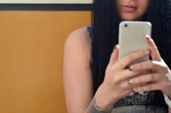 Brunettflickan tar selfie på en modern handlagsmartphone royaltyfria bilder