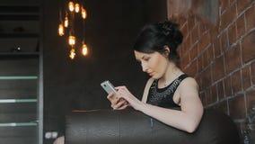 Brunettflickan tycker om en telefon på en lädersoffa arkivfilmer