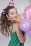 Brunettkvinna i ballonger och leende för ett födelsedaglockinnehav Arkivfoton