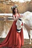 Brunettkvinna i en röd klänning med en krans av blommor Royaltyfri Fotografi