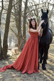 Brunettkvinna i en röd klänning med en krans av blommor Fotografering för Bildbyråer