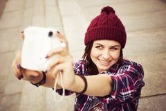 Brunettkvinna i hipsterdräktsammanträde på moment och taselfie på retro kamera på gatan tonad bild Royaltyfri Bild