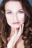 Brunettkvinna med blåa ögon utan smink, naturlig prickfri hud och händer nära henne framsida Fotografering för Bildbyråer
