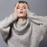 Brunettkvinna med bullefrisyren och det neutrala sminket som in poserar Royaltyfri Fotografi