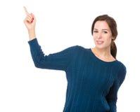 Brunettkvinna med fingerpunkt upp Arkivfoto