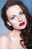 Brunettkvinna med för ögonskuggor för idérikt smink violetta fulla röda kanter, blåa ögon och lockigt hår med hennes hand på henn Royaltyfria Bilder