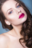 Brunettkvinna med för ögonskuggor för idérikt smink violetta fulla röda kanter, blåa ögon och lockigt hår med hennes hand på henn Arkivbilder