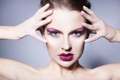 Brunettkvinna med för ögonskuggor för idérikt smink violetta fulla röda kanter, blåa ögon och lockigt hår med hennes hand på henn Arkivbild