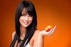 Brunettkvinna med nektarinen på orange bakgrund Arkivfoto