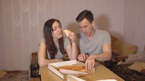 Brunettkvinna och man som hemma äter pizza stock video