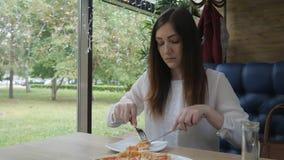 Brunettkvinna som äter pizza på ett kafé Snabbt och sjukligt banta lager videofilmer