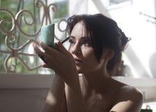 Brunettkvinna som applicerar sminket för framme av en spegel Royaltyfria Foton