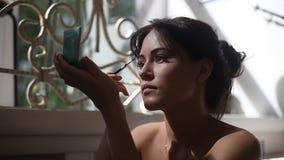 Brunettkvinna som applicerar sminket för framme av en spegel lager videofilmer