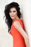 Brunettkvinna som bär den orange korta klänningen i stads- bakgrund Royaltyfria Bilder