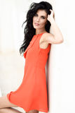 Brunettkvinna som bär den orange korta klänningen i stads- bakgrund Arkivfoto