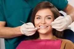 Brunettkvinna som besöker tandläkaren Arkivbild