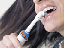 Brunettkvinna som borstar tänder med den elektriska tandborsten Fotografering för Bildbyråer