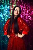 Brunettkvinna som firar och att ha gyckel på partiet Stående av en lycklig le flicka i en stilfull glamorös skinande röd klä fotografering för bildbyråer