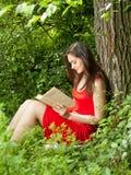 Brunettkvinna som läser en bok i parkera Royaltyfria Bilder