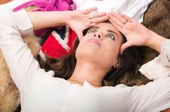 Brunettkvinna som ligger på högen av kläder som ler som naturligt som poserar shoppar modebegrepp Royaltyfri Foto
