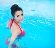 Brunettkvinna som poserar i en röd bikini som bär röd swimwear Royaltyfri Bild