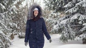 Brunettkvinna som promenerar en slinga i en vinterskog arkivfoton
