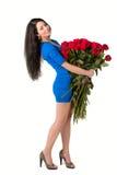 Brunettkvinna som rymmer en stor bukett av den röda rosen Royaltyfri Fotografi