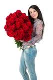 Brunettkvinna som rymmer en stor bukett av den röda rosen Royaltyfri Foto
