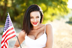 Brunettkvinna som rymmer USA flaggan utomhus- Royaltyfri Foto