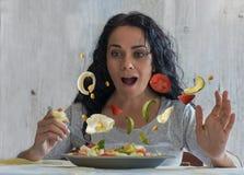 Brunettkvinna som ser förvånad som grönsakerna i hennes salladstart för att flyga royaltyfri bild