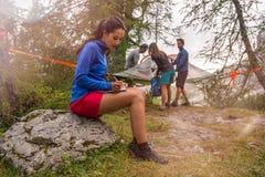 Brunettkvinna som skriver den personliga dagboken medan vänner som ställer in hängande campa för tält Grupp av vänfolksommar royaltyfria foton