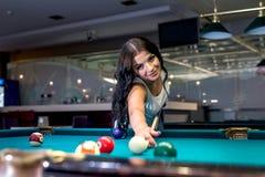 brunettkvinna som spelar billiard i bar arkivbild