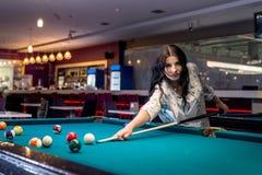 brunettkvinna som spelar billiard i bar royaltyfri foto