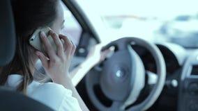 Brunettkvinna som talar på en mobiltelefon, medan köra en bil stock video