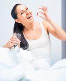 Brunettkvinna som tar en preventivpiller Arkivfoto