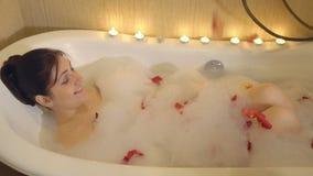 Brunettkvinna som tar ett bad med skum och rosa kronblad stock video