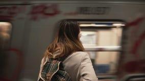 Brunettkvinnaanseende på järnvägsstation och vänta på hennes drev Flickan i tunnelbana på aftonen ser på snabba spårvagnar stock video