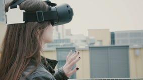Brunettkvinnaflickan med vinkande hår använder exponeringsglas för en virtuell verklighet på taket Royaltyfri Foto