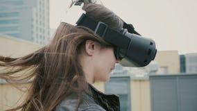 Brunettkvinnaflickan med vinkande hår använder exponeringsglas för en virtuell verklighet på taket arkivbilder