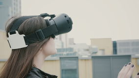 Brunettkvinnaflickan med vinkande hår använder exponeringsglas för en virtuell verklighet på taket 4K Fotografering för Bildbyråer