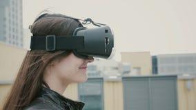 Brunettkvinnaflickan med vinkande hår använder exponeringsglas för en virtuell verklighet på taket 4K Arkivfoton