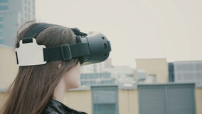 Brunettkvinnaflickan med vinkande hår använder exponeringsglas för en virtuell verklighet på taket 4K royaltyfri bild