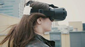 Brunettkvinnaflickan med vinkande hår använder exponeringsglas för en virtuell verklighet på taket 4K royaltyfri fotografi