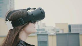Brunettkvinnaflickan med vinkande hår använder exponeringsglas för en virtuell verklighet på taket 4K royaltyfria bilder