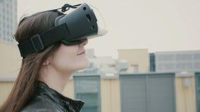 Brunettkvinnaflickan med vinkande hår använder exponeringsglas för en virtuell verklighet på taket 4K arkivbild