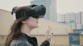 Brunettkvinnaflickan med vinkande hår använder hörlurar med mikrofon för virtuell verklighet 3D på taket 4K Arkivfoto