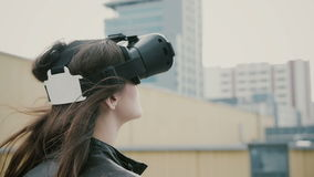 Brunettkvinnaflickan med vinkande hår använder hörlurar med mikrofon för virtuell verklighet 3D på taket 4K Fotografering för Bildbyråer