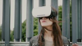 Brunettkvinnaflickan med vinkande hår använder virtuell verklighetexponeringsglas i det stads- utrymmet Arkivfoton