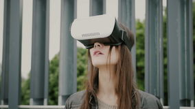 Brunettkvinnaflickan med vinkande hår använder virtuell verklighetexponeringsglas i det stads- utrymmet royaltyfria bilder