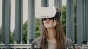 Brunettkvinnaflickan med vinkande hår använder virtuell verklighetexponeringsglas i det stads- utrymmet 4K arkivfoto